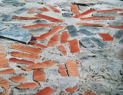 Lo strato di preparazione con i frammenti di anfore su cui erano fissate le lastre di marmo (da Domus dei Tappeti di Pietra, guida edita da RavennAntica, Ravenna 2008, p. 34)